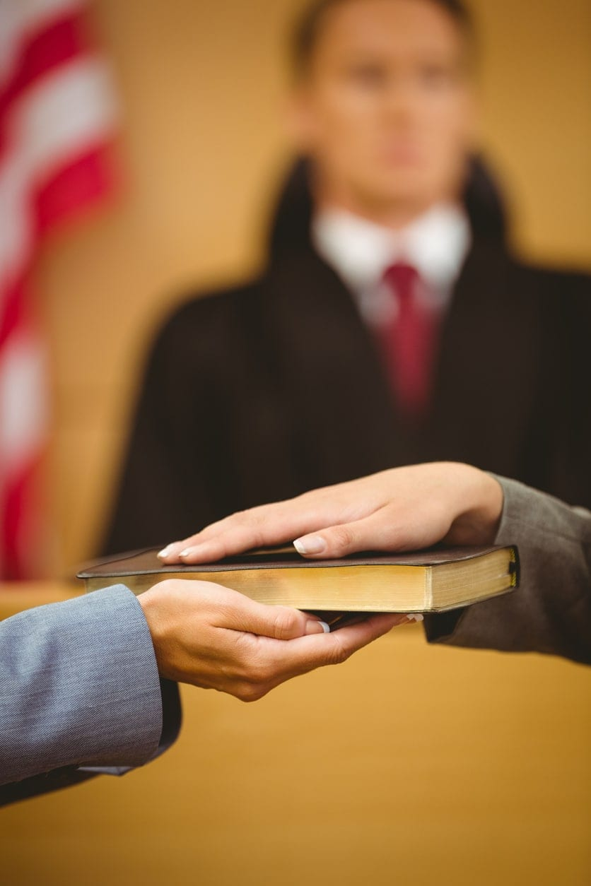 Một nhân chứng chuyên nghiệp thề thốt về Kinh Thánh trước tòa.